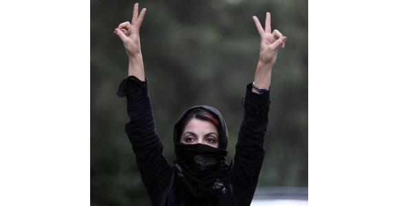 An Iranian woman holds her hands in the air and makes V signs as she protests in the streets on July 9, 2009 in Tehran - Source: Getty Images.